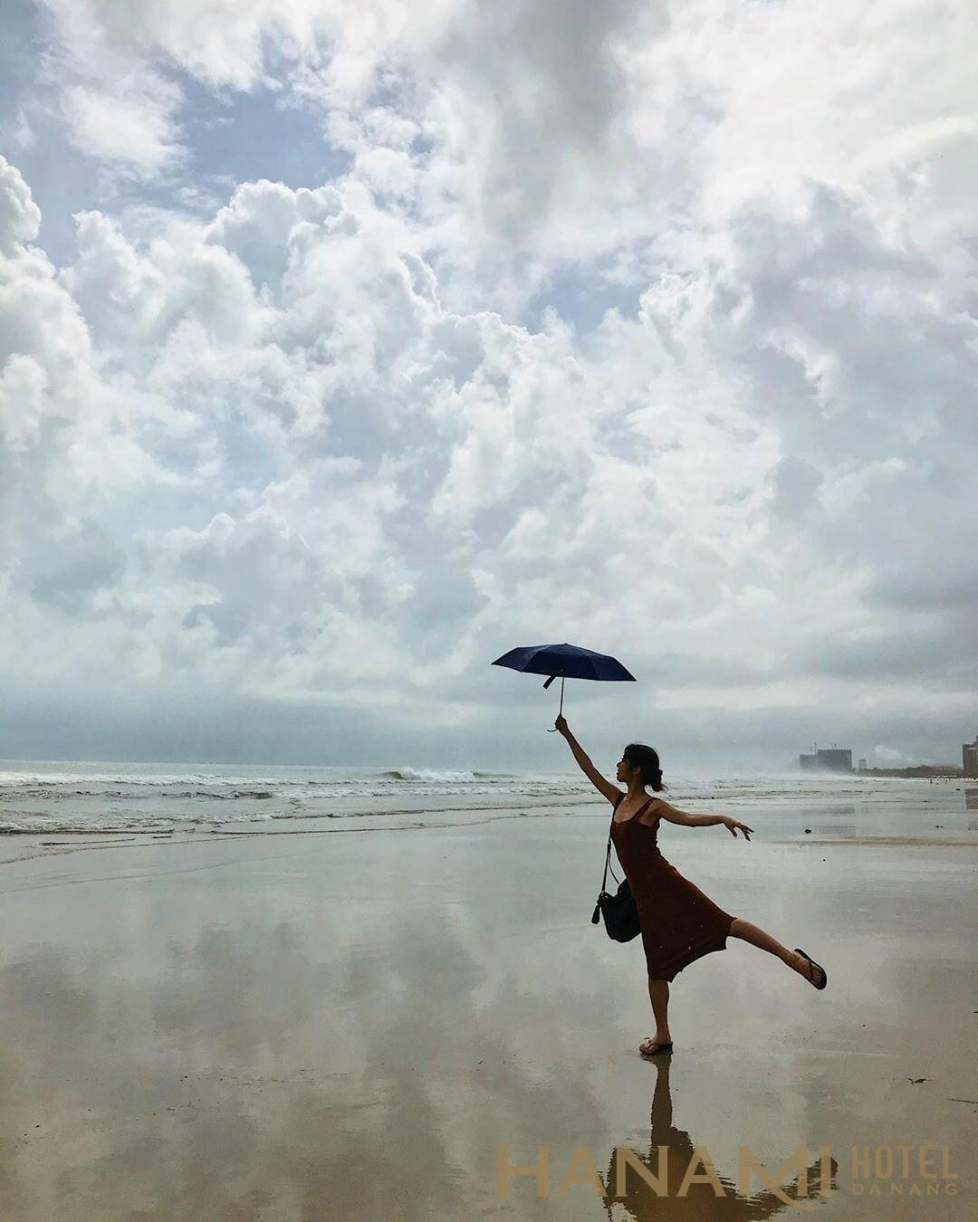cô gái cầm ô chụp hình ở bãi biển mỹ khê