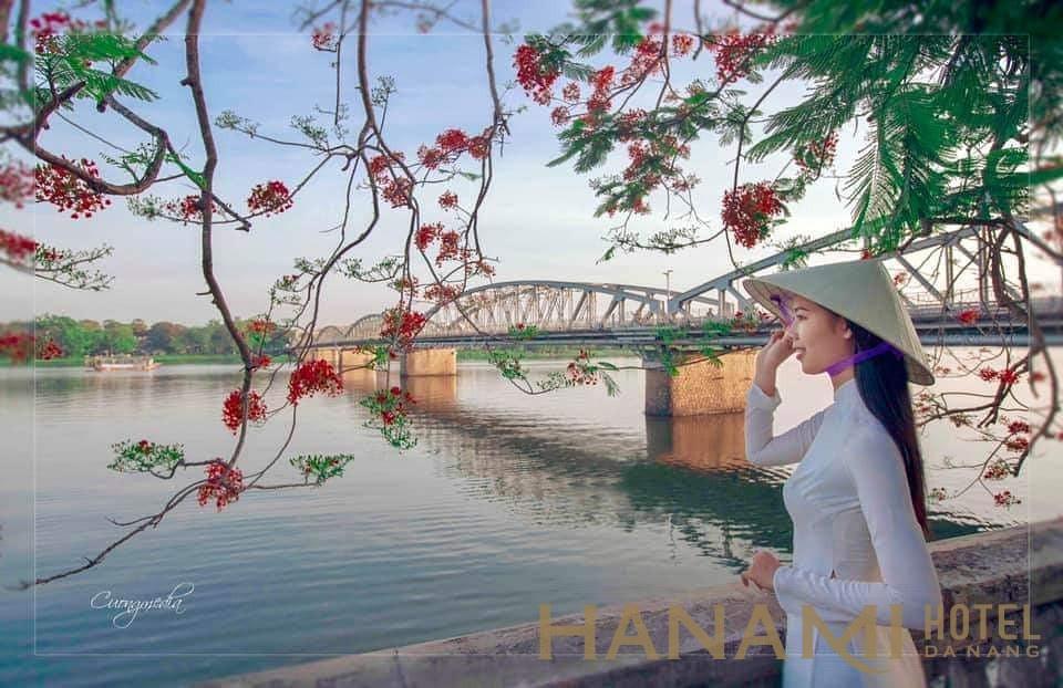 nữ sinh mặc áo dài bên cạnh cầu Tràng Tiền